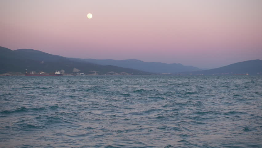 Beautiful sunset, rising moon over sea and mountain, hand shot.