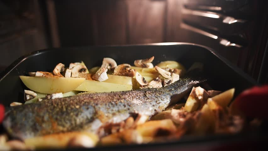 Slow motion of hands with silicone gloves putting baking pan with raw ingredients to the heated oven. Trout fish with potatoes and champignons. The cook puts pan with raw ingredients to the heated ove