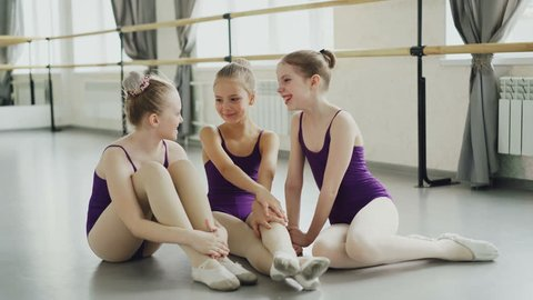 Emotional children are having rest after ballet lesson sitting on floor in light studio, talking and laughing. Happy childhood, dancing school and interior concept.