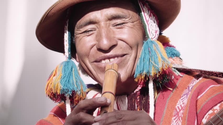 Native quechua man using a colorful handcrafted chullo and a highlander hat, singing with his guitar on the alleys of Cusco | Shutterstock HD Video #1011161774