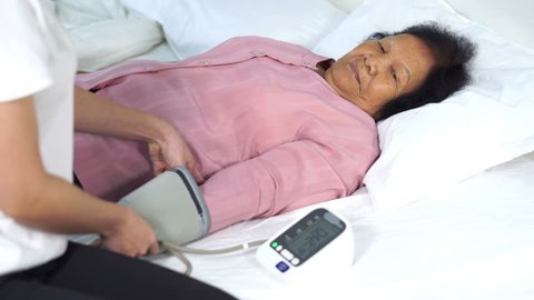 female nurse checking blood pressure of a senior woman on bed