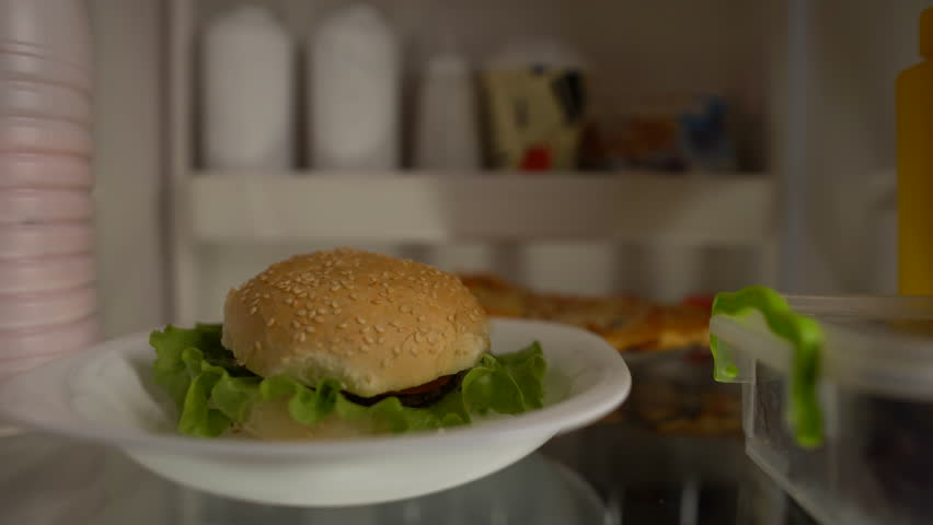 Fat hungry man taking hamburger from fridge and eating eagerly, diet failure | Shutterstock HD Video #1011222584