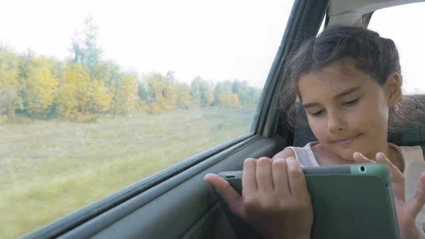 Beautiful little girl are using a tablet with an open digital map in it, talking and smiling. girl teen sitting in the car in the back seat travel . little girl bored in the car. concept kid car long