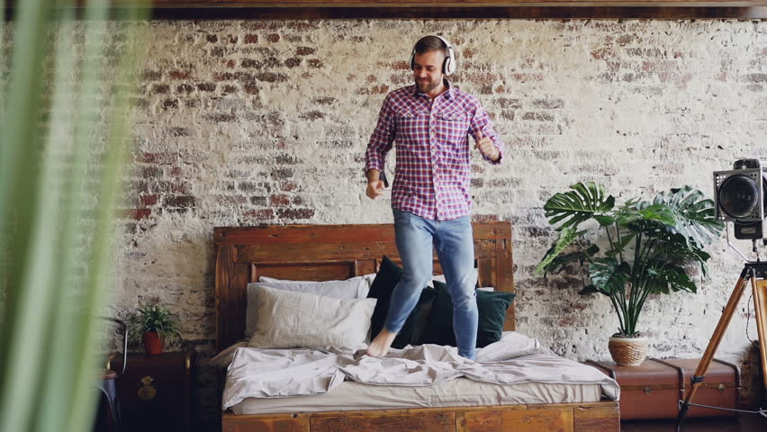 Slow motion of handsome bearded guy have fun jumping dancing on bed and listening to music in headphones. Modern loft style apartment and plants are visible.
