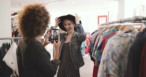 Millennial trying on a hat in a vintage clothing store