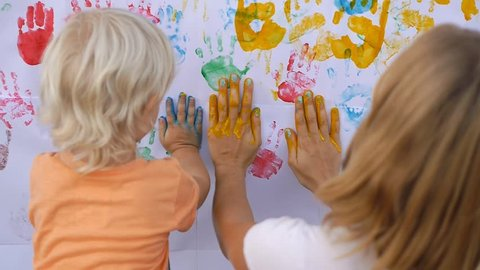 Cute little child painting color handprints on the white wall with mother together. 50fp