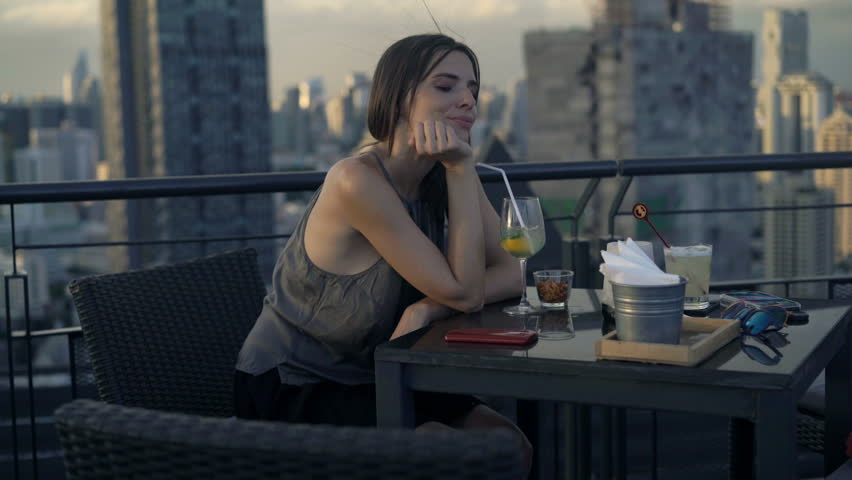 Pensive, young woman drinking cocktail in skybar   | Shutterstock HD Video #1011288344
