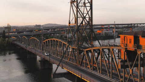 Drone aerial tracking style shot of the Hawthorne Bridge with a bus crossing at sunrise in Portland Oregon