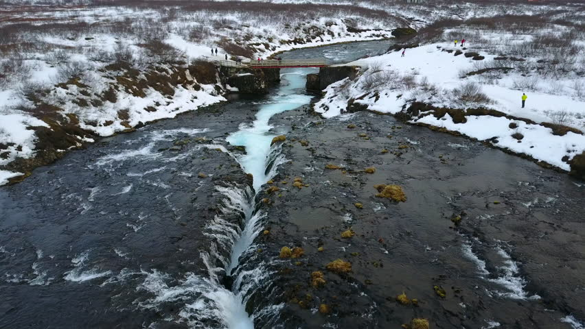4K. Aerial view over Bruarfoss waterfall. Flowing of turquoise water and surrounded by fresh snow of winter. famous destination in South Iceland   Shutterstock HD Video #1011290774