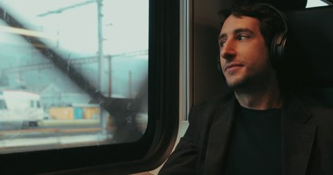 Man riding train listening to music, podcast, or audiobook while riding train  and looking out window