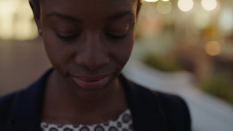 close up portrait of pretty african american business woman looking at camera serious confident wearing nose ring in evening city background light bokeh