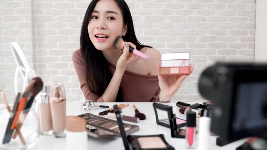 Young beautiful Asian woman professional beauty vlogger or blogger recording make up tutorial to share on social media   Shutterstock HD Video #1011308804