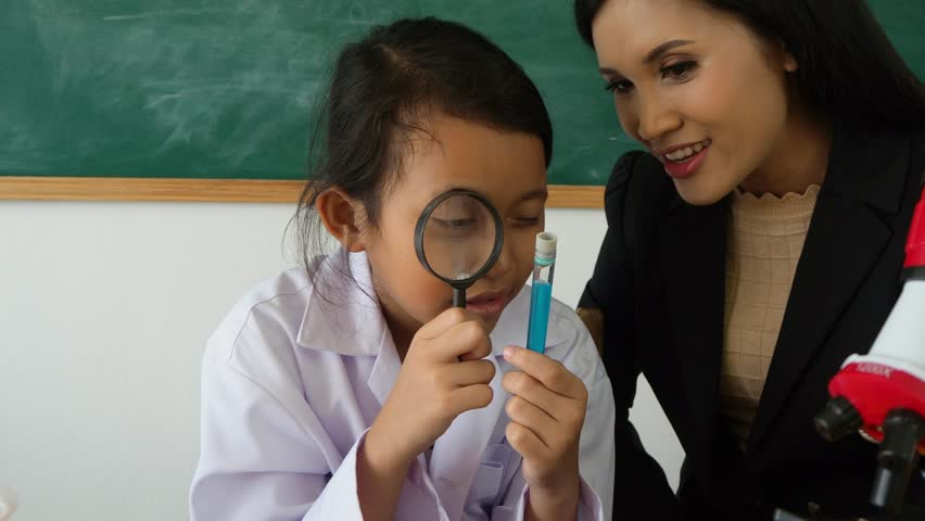 Young asian schoolgirl looking liquid in tube thru magnifying glass in classroom | Shutterstock HD Video #1011310574