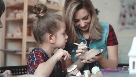 A little girl is making a clay craft in a pottery workshop. Mom and child spend time together doing creative work