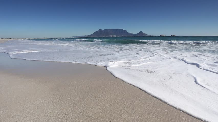 Wide angle view of waves washing up on the white sands beach on Cape Town South Africa with Table Mountain in the distance.