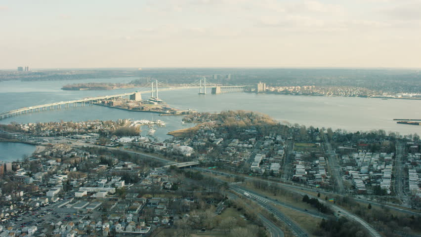 Aerial view of large city. Flying over river towards bridge in New York. Shot with a RED camera.