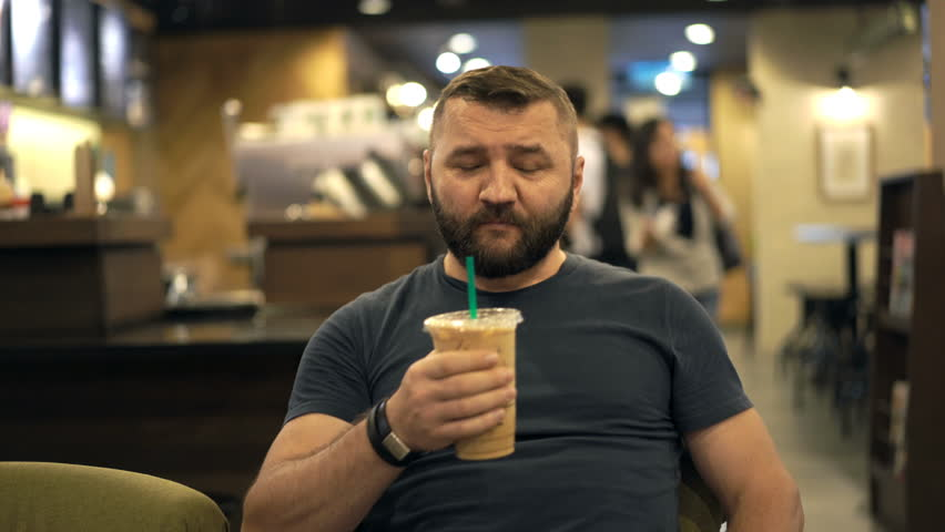 Happy, young man drinking ice coffee sitting in cafe  | Shutterstock HD Video #1011354344