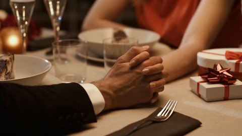 Romantic loving couple having a dinner date at the restaurant and celebrating with gifts, they are joining their hands, relationships and feelings concept