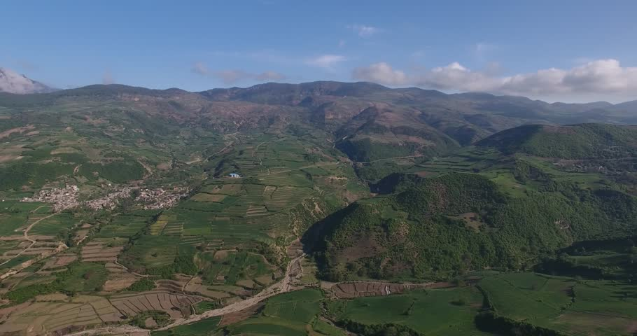 Aerial long shot over mountains covered with barley canola wheat farms 6 scenic landscape of mounatains on horizon vivid cinematic filter 4k raw footage   Shutterstock HD Video #1011357464