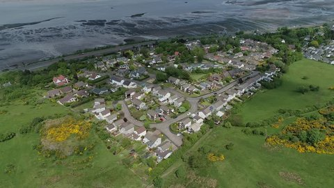 Aerial footage of the village of Langbank on the south shore of the Firth of Clyde flying to the right over woodland and yellow gorse covered hillside.