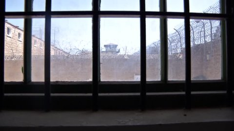 Tilt up from darkness to looking out a barred prison window at the fenced prison yard