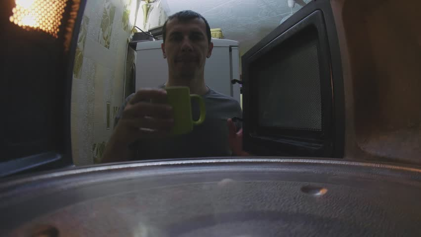 Man warms coffee in microwave oven lifestyle first-person view a indoors   Shutterstock HD Video #1011372674