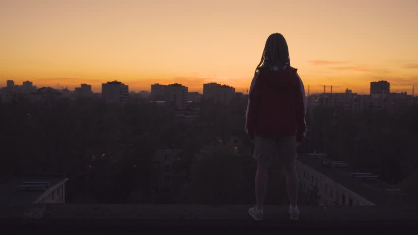 Back view of woman with dreadlocks standing on roof and rising up her hands   Shutterstock HD Video #1011379724