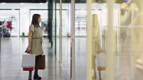Front view tracking shot of young woman with paper bags walking along shopping mall hallway and stopping to look into store window