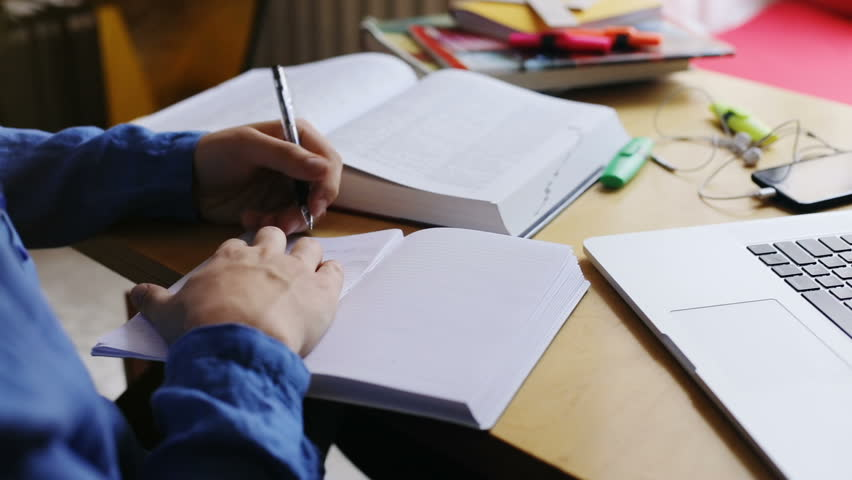 close-up view of male hand using pen writing text in diary with opened book and modern technology