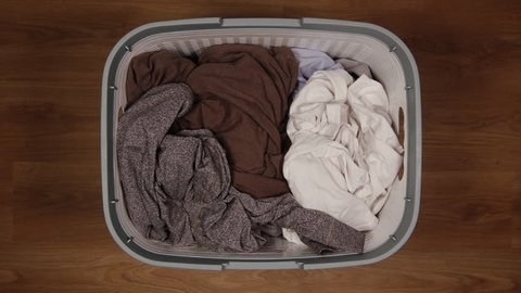 TOP VIEW: Dirty clothes are filling a laundry basket on a floor - Stop Motion