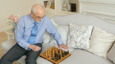 Elderly grandmaster plays chess alone, old man playing chess