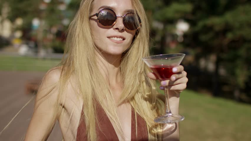 5e5118eb44 beautiful blonde brown-eyed with long hair girl smiling turn around and  dissolve the hair and send air kiss in brown swimsuit and bikini with  wineglass of ...