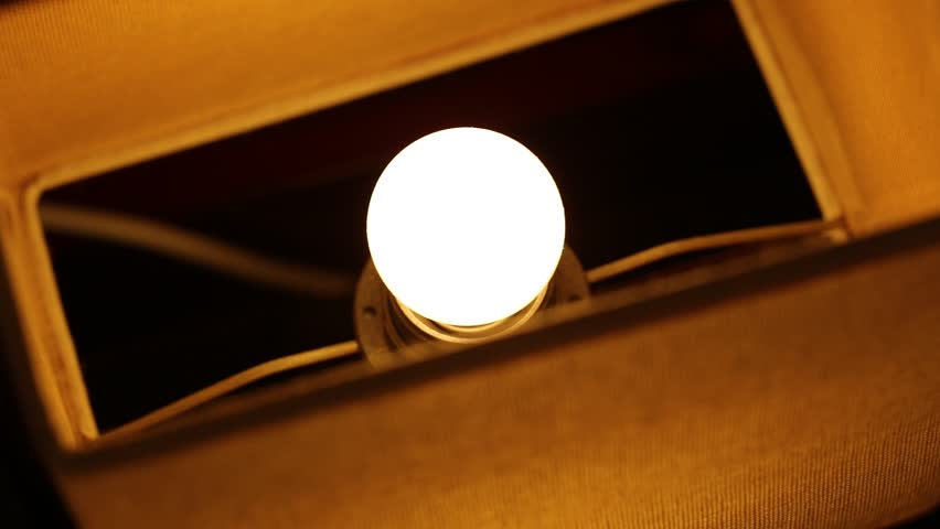 Closeup top view of lamp inside of lampshade. Turning light on and off using dimmer control.