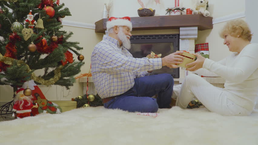 Old woman and man lie on the fluffy carpet and exchange Christmas presents | Shutterstock HD Video #1011438764