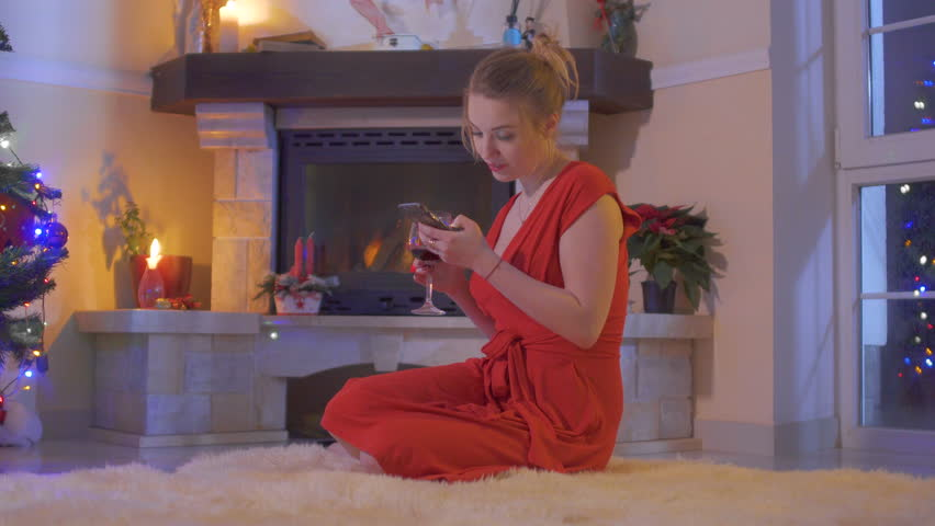 Young girl in red dress sit on floor near Christmas tree and using her phone | Shutterstock HD Video #1011439004