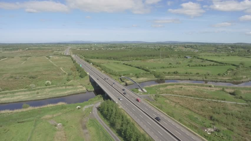 aerial birds eye view of a busy irish motorway with bridge crossing a water river and railway track in ennis county clare, ireland