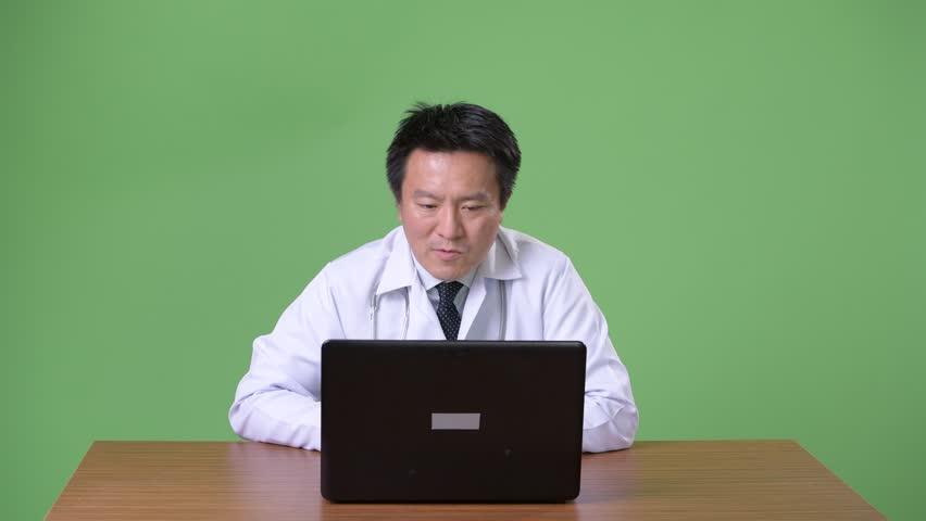 Mature Japanese man doctor against green background | Shutterstock HD Video #1011457124