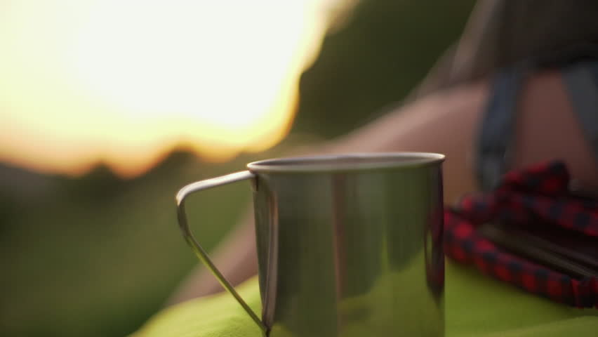 Countryside closeup view with focus on metal cup of hot steaming coffee or tea, during blurry sunset in slow motion. Travel concept | Shutterstock HD Video #1011459074