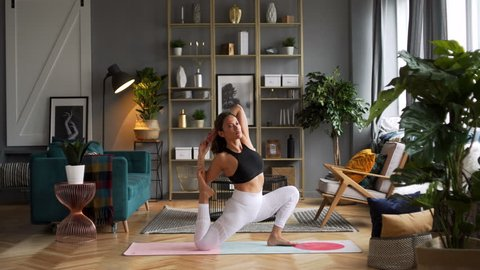 Attractive Caucasian woman in her thirties does yoga poses bend dog in the morning in stylish sunny spacious living room in elegant Scandinavian style decorated with sophisticated decor
