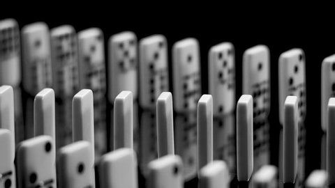Two rows of white dominoes falling in slow motion. The first row falls from left to right, then the second row falls from right to the left.