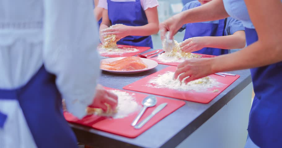 Children or teenagers in the kitchen knead the flour with the egg to get the dough. Close-up of hands | Shutterstock HD Video #1011485414