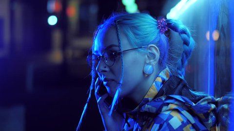 Attractive pretty girl with unusual hairstyle near glowing neon lights of the city at night talking with smartphone. Dyed blue hair in braids. Happy hipster teenager using mobile.