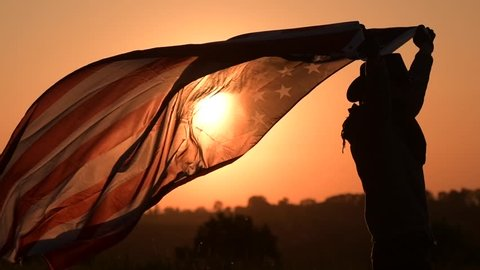 Slow Motion Footage of Caucasian American Cowboy Patriot Running with Flag During 4th of July Independence Day Sunset.