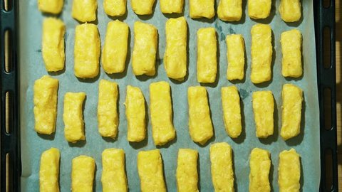 Potato and cheese sticks on a baking tray. Lubricate with vegetable oil.