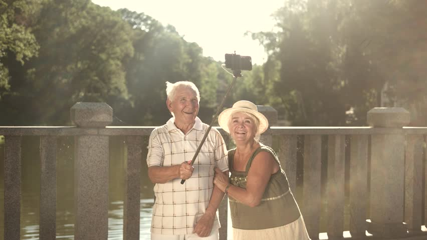Cute couple of seniors taking a selfie. Elderly man and woman with monopod on nature background in sunny day. Old people and gadget.