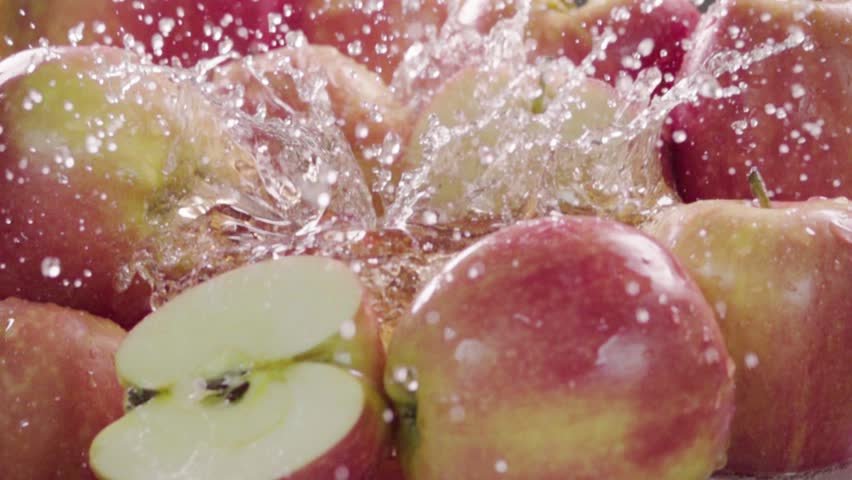 Red apple falling in juice with splash between apples. Slow motion
