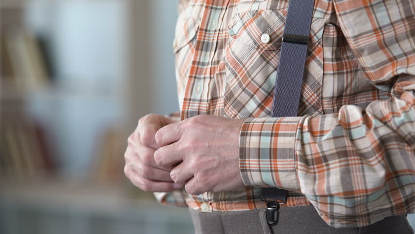 Old man with trembling hands buttoning up shirt, beginning of Alzheimer disease