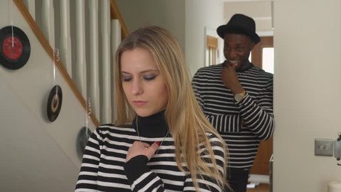Man Laughing behind girlfriends back. Handheld shot of white girlfriend being laughed at by black boyfriend indoors - wearing matching outfits