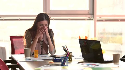 Female office worker having an headache. Woman took pills to get rid of headache and continue working.
