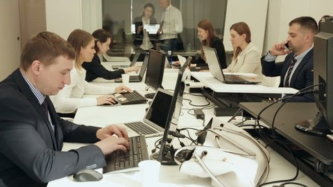 Successful coworkers engaged in business activities in busy open plan office